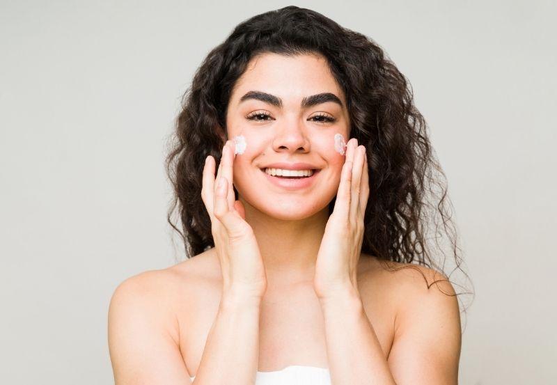 modella che si idrata per la cura della pelle del viso